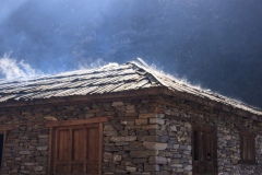 Smoke rising through the roof of a house in Khote.