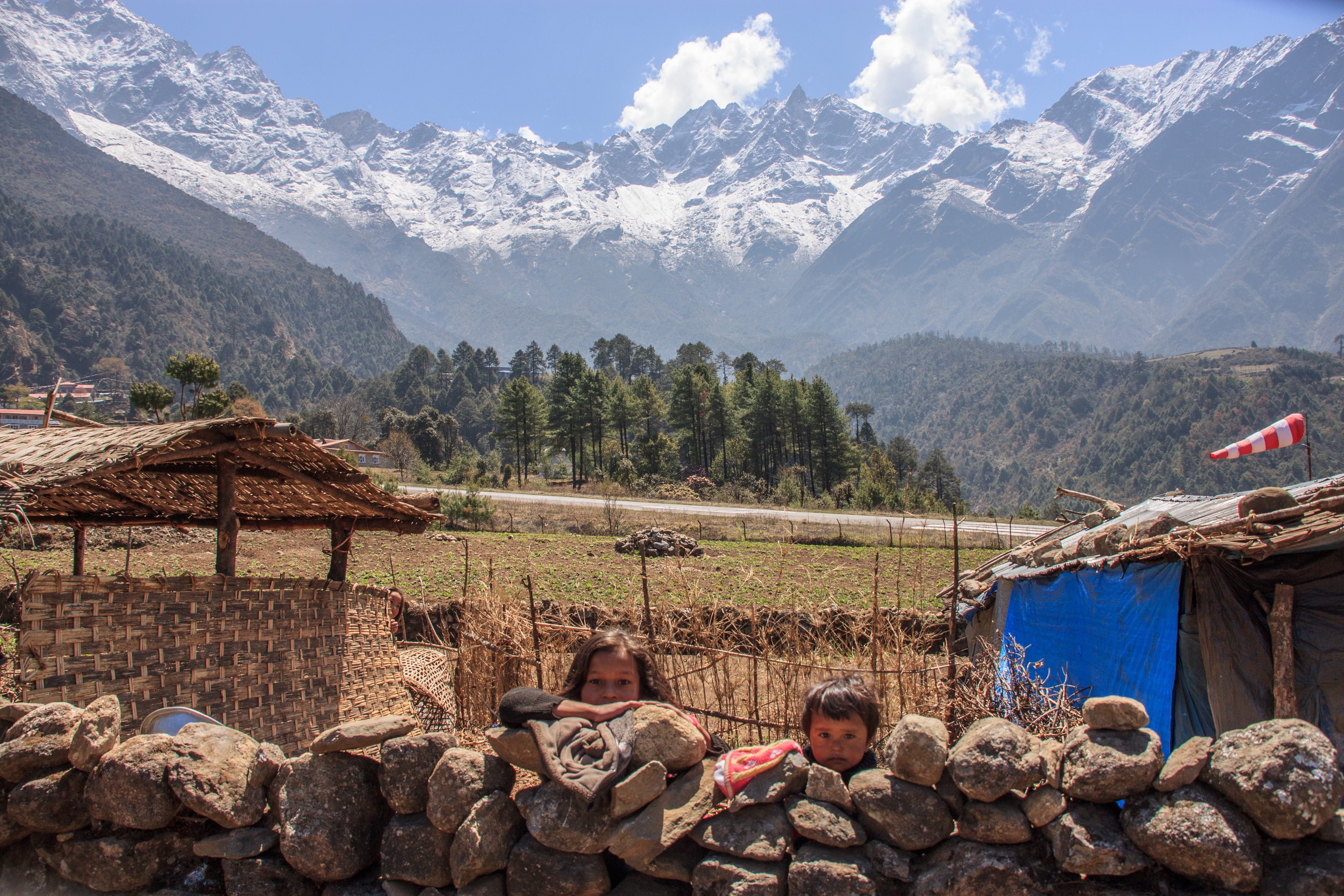 Children and the runway at Lukla with the Zatwa La (pass) in the background.