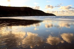 Baggy Point and evening clouds reflected on Putsborough Beach