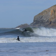 Surfer in Croyde Bay with Baggy Point in the background