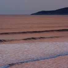 Evening light reflected in the sea off Putsborough with Morte Point beyond. March 2013.